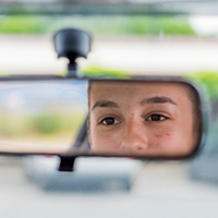teen girl in car rearview mirror